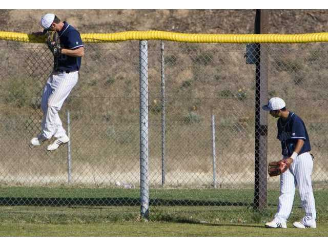 Saugus center fielder Stefan Cordes attempts to rob a home run as teammate Tommy Meza watches.
