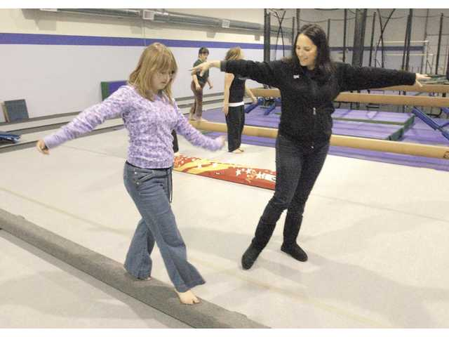 Gymnastics Unlimited co-owner Lisa Eichman works with Melissa Grayon, 15, on the balance beam as she learns gymnastics movies at a Special Olympics class held at the Valencia gym.