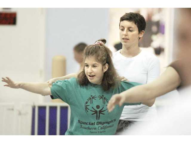 Coach Sash Spivak, right, works with Tamara Wilson during a gymnastics training session held at Gymnastics Unlimited in Valencia. The gym is the official training center for Santa Clarita Valley Special Olympics gymnastics training in preparation for the summer games.