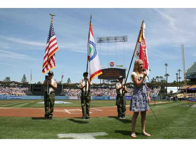 With the color guard from Boy Scout Troop 2222 standing behind her, singer/actress Camille Gray, 12, of Stevenson Ranch, sings the National Anthem during SCV Dodger Day ceremonies Sunday before the Dodgers' game against the Colorado Rockies.