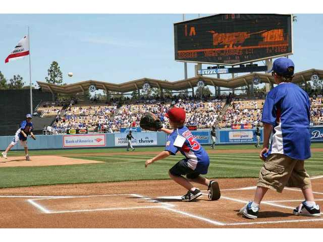 Pitcher Devin Sifers (left), catcher Tyler Hodge (center) and umpire Riley Witt (right) from the William S. Hart baseball program throw out the ceremonial first pitch during SCV Dodger Day ceremonies at Dodger Stadium before Sunday's game between the Dodgers and the Colorado Rockies.