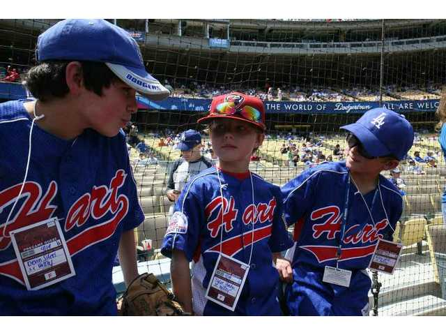 Pitcher Devin Sifers (left), catcher Tyler Hodge (center) and umpire Riley Witt (right) from the William S. Hart baseball program get ready to throw out the game's first pitch at Dodger Stadium during SCV Dodger Day opening ceremonies Sunday.