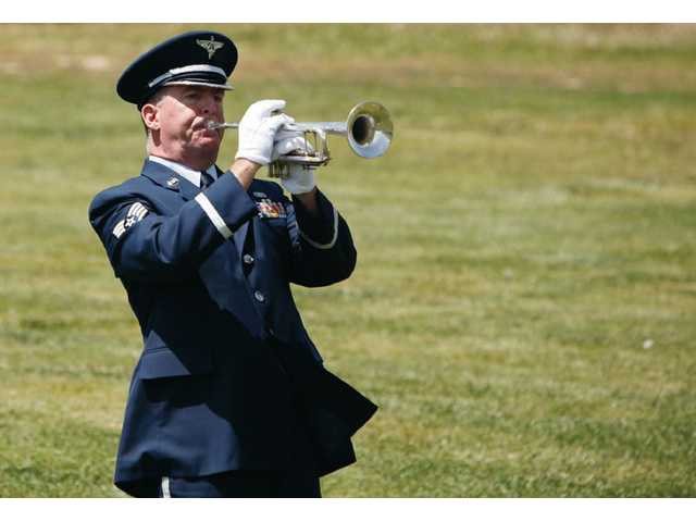 Air National Guard Staff Sgt. Robert Goodwin plays Taps on the trumpet during the memorial service.