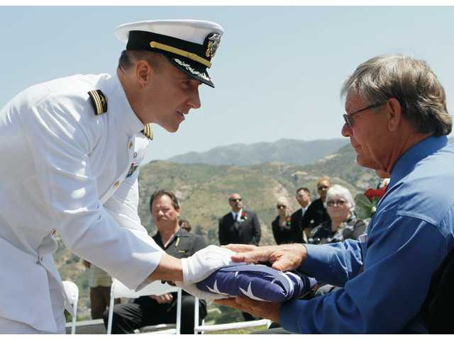 U.S. Navy Commander Christopher Scholl, left, hands a folded flag to Robert Good, a Bronze Star recipient in the Vietnam War, near the end of the ceremony. Good will take the flag and a display of the men's names to the veteran's center in Sepulveda.