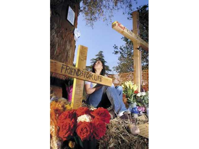 SueAnn Sagehorn sits at the makeshift memorial for her boyfriend, James Neill. He died in a car crash onApril 16. More than 400 mourners attended Neill's funeral Thursday.