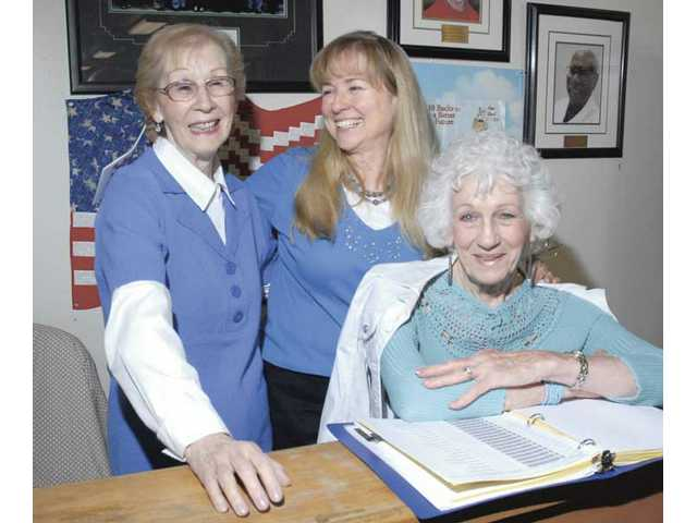 Volunteers Cecil Bernstein, left, and Bea Mulligan, right, join Director of Volunteers Robin Clough, center, at the information desk of the SCV Senior Center for National Volunteer Week on Thursday.