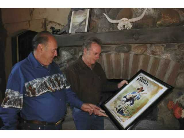 At the hearth in their rustic production office at Melody Ranch, Andre and Renaud Veluzat take their first look at the poster art created by Buck Taylor for the 2008 Santa Clarita Cowboy Festival, the 15th the family has hosted at the working studio.