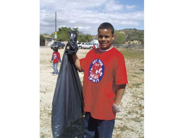 Jordan Zavala, 14, takes part in the Neighborhood Clean-Up at the Newhall Community Center April 11. More than 160 local youth and adult volunteers participated in the program.