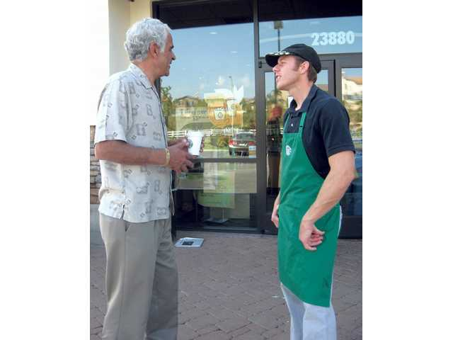 Valencia resident Aziz El-Farra speaks with Starbucks barista Adam Barlow on Wednesday. The store on 23880 West Copper Hill Drive will close on May 8.