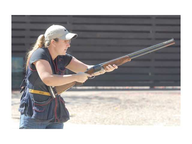 Four-time Olympic Medalist Kim Rhode practices before her trick shot exposition at the fundraiser.