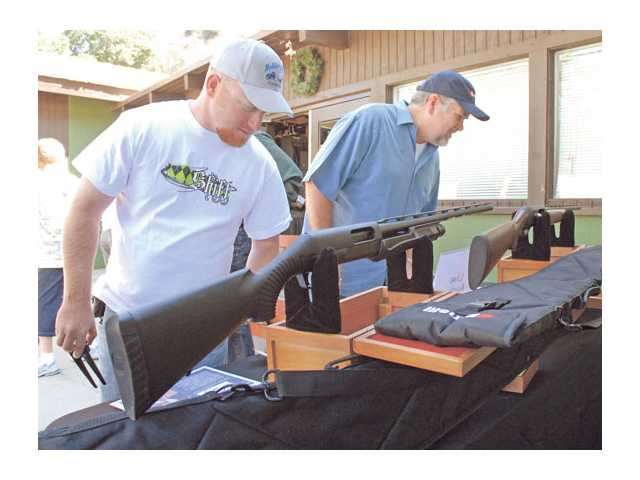 Brian Ridlon, left, and Marty Hansberger check out two shotguns available for auction Friday at the How the West Was Won Trap Shoot Competition fundraiser at Carousel Ranch.