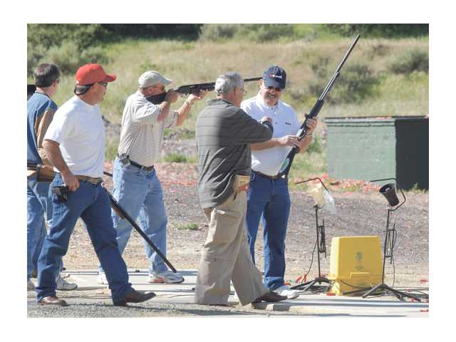 Wayne Crawford, right, works with first-time shooters at the How the West Was Won Trap Shoot competition fundraiser for Carousel Ranch at Oaktree Gun Club on Friday.