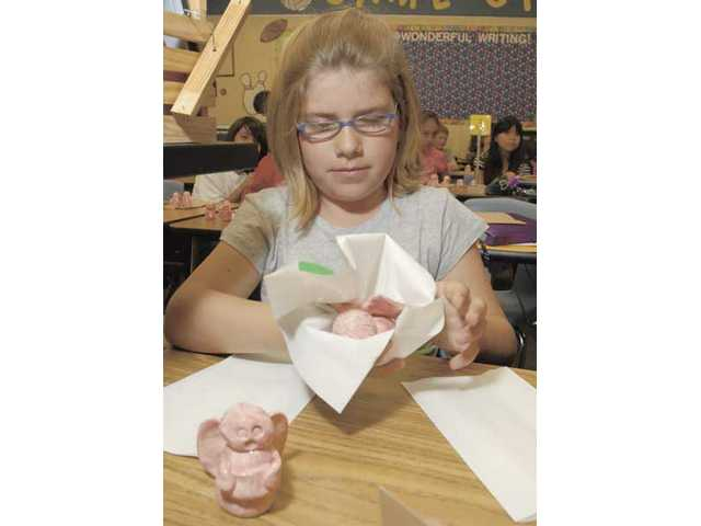 Highlands Elementary School fifth-grader MacKenzie Taylor wraps her clay angels to give to her uncle and grandmother as she finishes her work on the Angels Project on Wednesday. The students made more than 500 clay angels to give to loved ones.