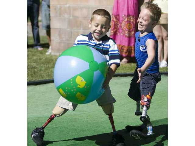 Cameron Lutges, left, and friend Cody McCasland play together before McCasland presents Lutges with the new prosthetic legs as a birthday gift Monday morning.