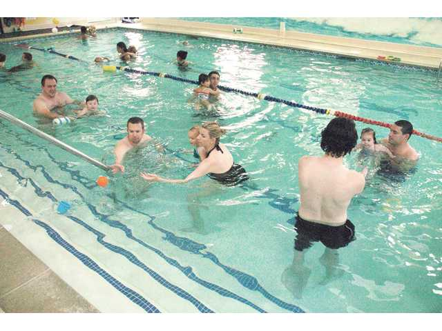 Parents and swim instructors teach their kids to swim together at the Academey Swim Club.