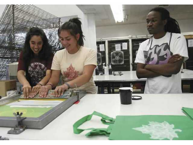 Lorin Brown, right, a second-year Cal Arts graphic design student, oversees the silkscreening techniqueof Academy of the Canyons senior Priscilla Sahagun-Guevara, middle, and West Ranch senior Elizabeth Alexander on Tuesday.