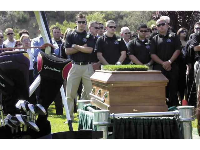 Friends and family listen to eulogies for James Neill at Eternal Valley Memorial Park and Mortuary on Thursday afternoon. Neill died on April 16 when he lost control of his vehicle on Hasley Canyon Road near his home. Neill was an avid golfer so his friends placed some grass and a golf ball on his casket.