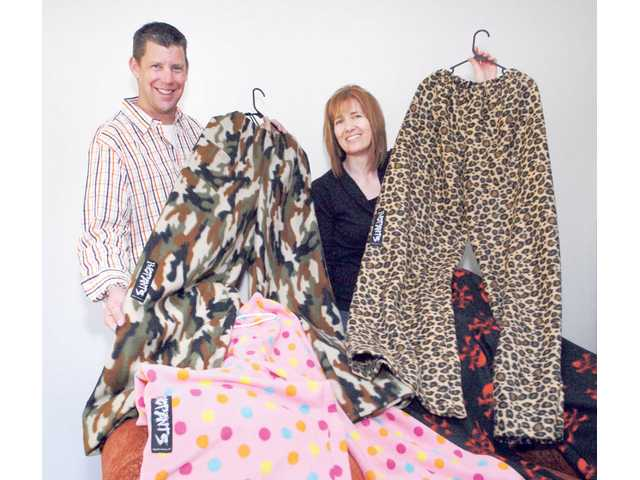 "Original Big Pants partners, Dean Robertson and Lorelai Dunbar of Valencia display samples of their product in Military Camo and Lazy Leopard patterns . Dunbar invented the pants which are a cross between ""your favorite blanket and your most comfy PJs."" The pants are one size fits all and retail for $35 per pair."