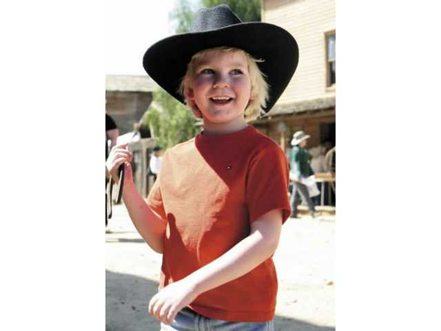 Connor Dean, 5, from Stevenson Ranch, smiles after getting his name engraved on a horse shoe Saturday afternoon at the Cowboy Festival.