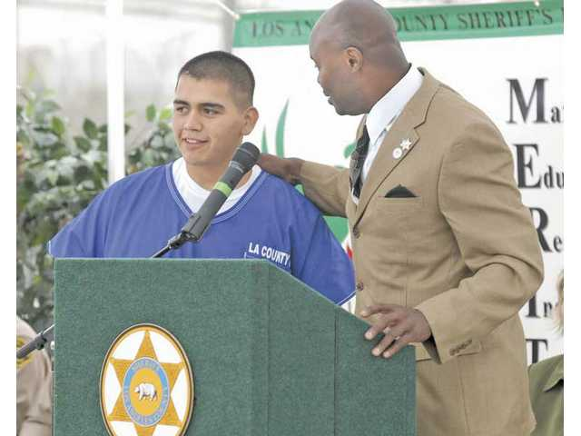 MERIT Program instructor James Beard, right, introduces graduate Ruben Flores to the microphone at graduation ceremonies for the MERIT Program at Pitches Detention Center on Thursday. More than 75 inmates received certificates for participating in the program.