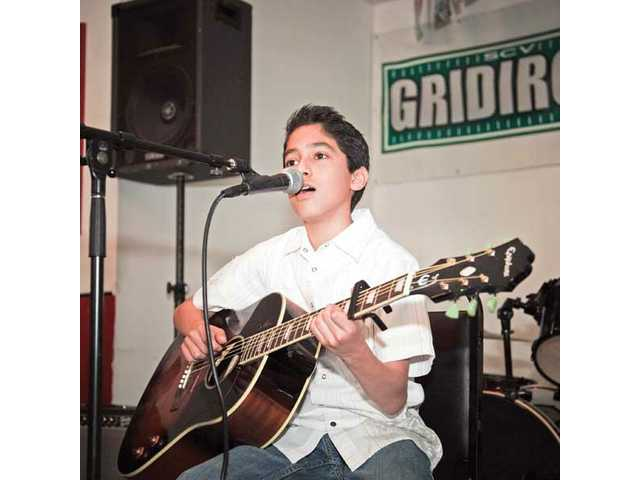 Steven Gudino plays the guitar and sings during a performance.