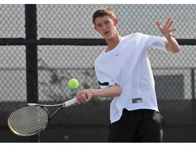 Valencia's Tayven Townsend, left, returns a shot as teammate Dalton Ullman, right, watches during their doubles match against Canyon on Tuesday at Valencia High School. The Vikings won 17-1 to secure their eighth straight Foothill League championship.