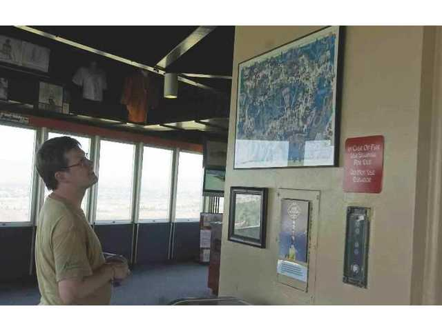Skogstad Forerkort, from Norway, is spending his summer vacation touring all of the Six Flags parks in North America. Here he is looking at one of the old maps and pictures on display at the Sky Towers museum at Six Flags Magic Mountain.