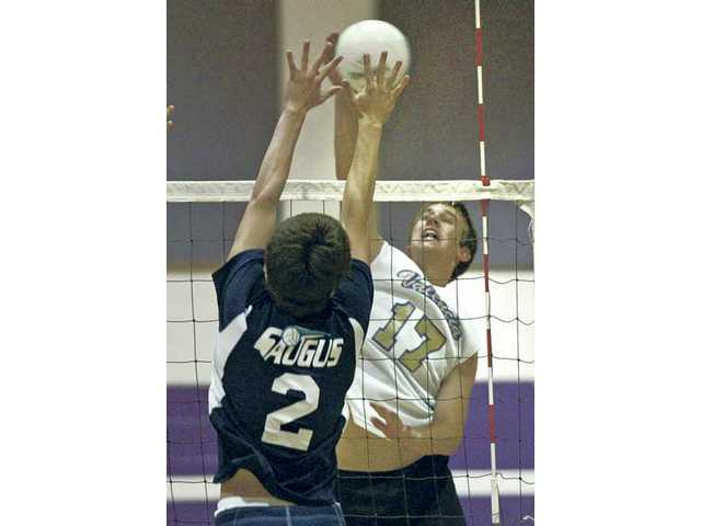 Daniel Johnson (17) of Valencia spikes the ball against Mike Romero of Saugus at Valencia of Tuesday.