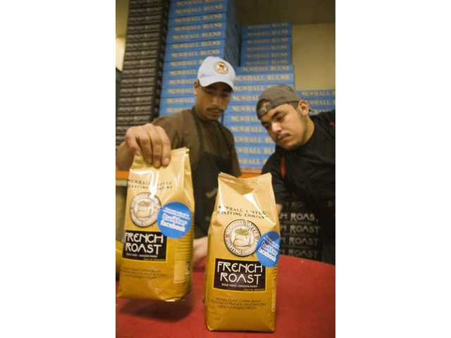 (Left to right) Brothers Angel and Jose Martinez are in charge of packaging, organizing and boxing freshly roasted Newhall Coffee.