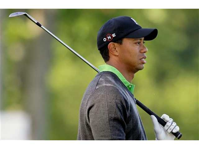Tiger Woods watches a shot on the 14th hole during the first round of the Quail Hollow Championship golf tournament at Quail Hollow Club in Charlotte, N.C., Thursday, April 29, 2010.