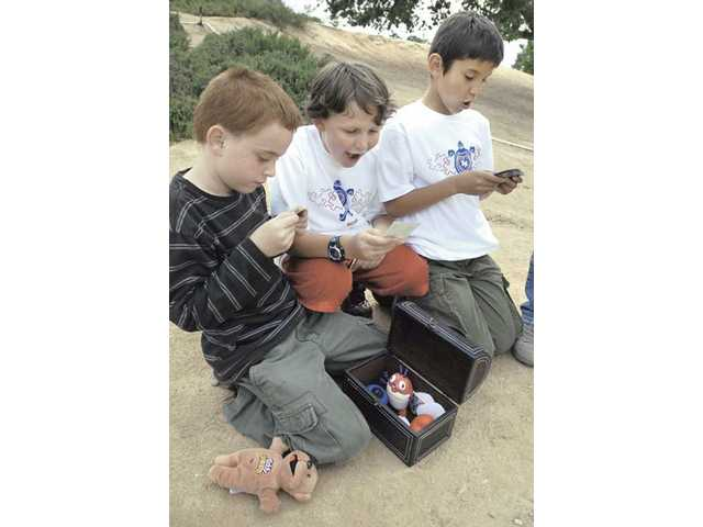"Frankie Peters, Ty Heid, and Angel Gutierrez pull trading cards and toy characters from their ""treasure chest"" as they play together at Heritage Park on Friday."