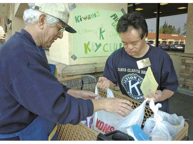 Bill Tozzi, left, of the Kiwanis Club of Santa Clarita and Chandler sort bags of food into the four shopping carts.