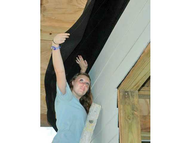 Samantha Spigelman puts tar paper under the eaves of one of the houses the youths worked on during the week. Nine teens from the First Presbyterian Church in Newhall spent eight hours a day for seven days building two houses in the Bahamas. The trip was facilitated by Next Step Ministries.