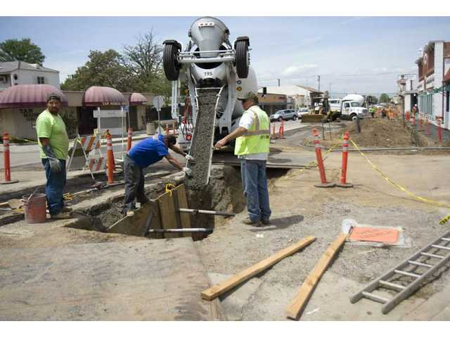 Mike See, left, John Collini and Dan Wilkins work on structuring the storm drain underground on Main Street in downtown Newhall on Friday afternoon. The streetscaping work is scheduled to be complete in time for the city's July 4 parade.