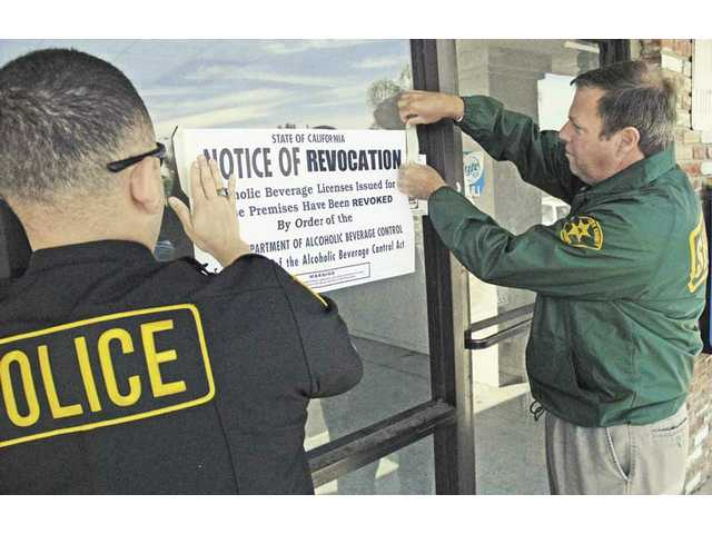 An undercover officer from the Alcohol Beverage Control Police, left, and Santa Clarita Valley Sheriff's Department Lt. Steve Low post a notice of license revocation at Smoke-N-Cerveza in Newhall Thursday.