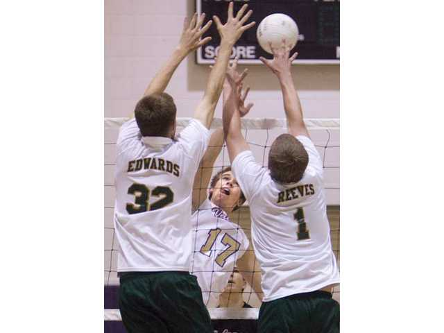 Valencia's Daniel Johnson (17) attacks at the net against Canyon's Mike Edwards (32) and Alex Reeves (1) Thursday at Valencia High.