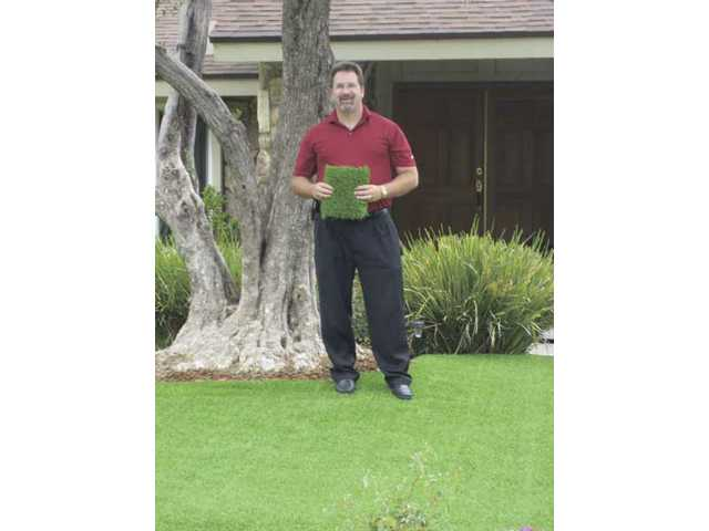 Shawn Green stands on his new front lawn, holding a square of the Top Cut synthetic lawn material.