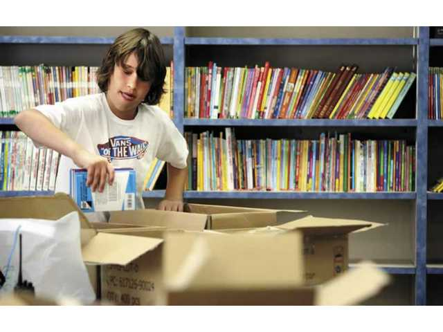 Sixth-grader David DiCicco, student council president at Sulphur Springs Elementary School, helps put books on the shelves of the library at Golden Oak Elementary School which will open in Canyon Country next fall.