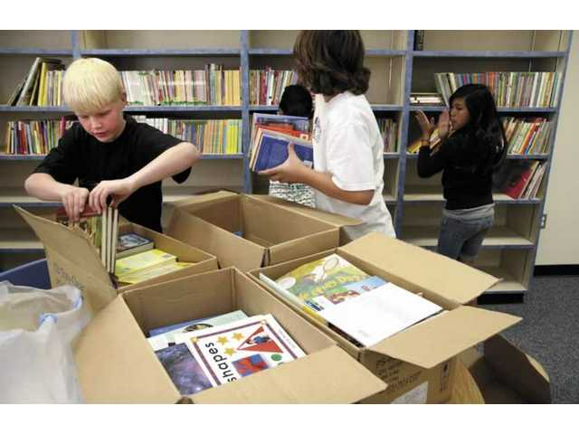 A sixth-grader from Sulphur Springs Elementary School and student council members help stack up the some of the 800 books they collected for the future library at Golden Oaks Elementary School.