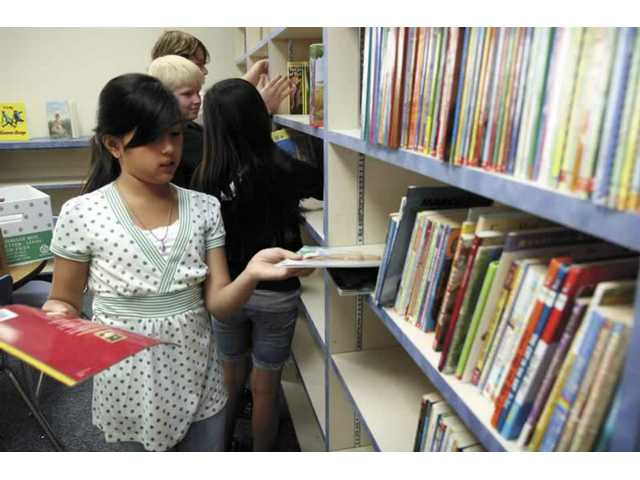 Danika Sardello, a sixth-grader from Sulphur Springs Elementary School, helps shelve books at GOlden Oaks Elementray School library Thursday morning. Students collected over 800 books for the future school, which will open next fall.