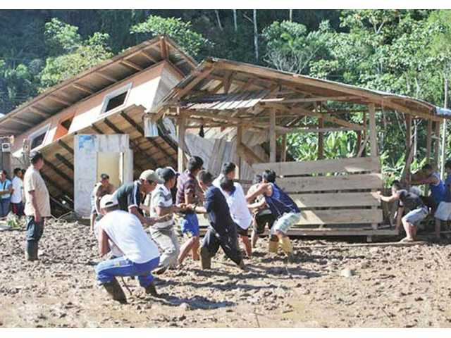 A neighborhood works together to pull a house back on to its foundation in Tena, Ecuador, which is one of Santa Clarita's sister cities. The city was recently ravaged by mudslides and flooding.