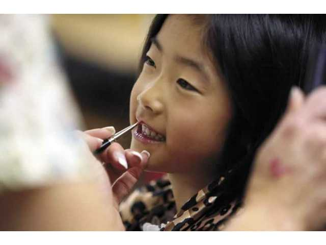 Kindergardener Natalie Choo gets her make-up done by professional makeup artist and mom, Valerie Riccardi, at Bouquet Canyon Elementary School's Career Day.