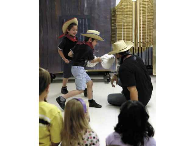 "Kyle Mattox swings a fake bank bag full of money, ""striking"" stuntman Mark Riccardi in the face during a skit Friday morning which helped illustrate the career of a movie/television stuntman. Friday was career day at Bouquet Canyon Elementary School."