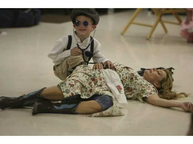 Jarod Griswald rushes to the aid of a damsel in distress during a skit performed at Bouquet Canyon Elementary School's Career Day.