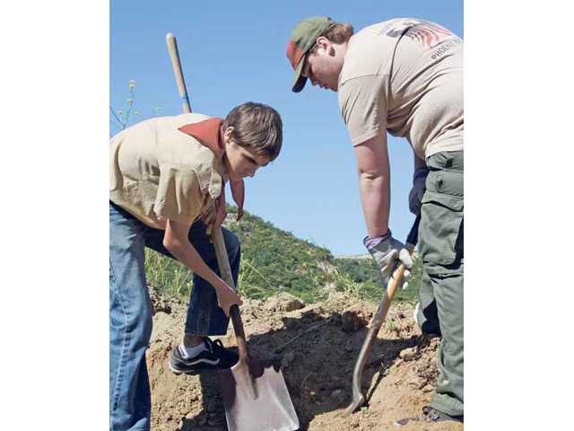 Tyler Finley, 15, left and Ryan Leinbach, 16, from Boy Scout Troop 585 help remove dirt and debris from the grounds of the Santa Clarita Emergency Winter Shelter for Austin Leinbach's Boy Scout Eagle Project on Saturday.