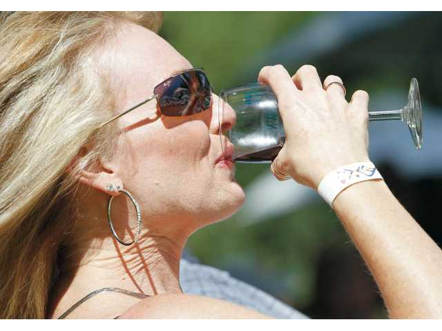 Nancy Totta, of Valencia, drinks a glass of petite sirah wine from Trader Joe's as she and her friends spend the afternoon at Taste of the Town.