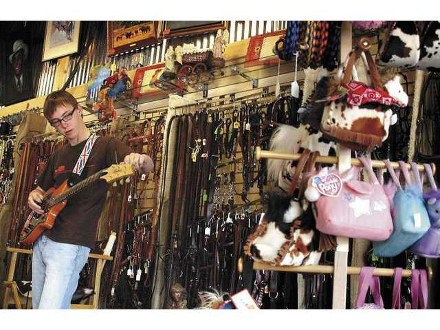Henry Webster, 16, tunes up for the jam session Sunday at Rattlesnake Slim's in Newhall. The store sellscoffee, tea and gear for horses.