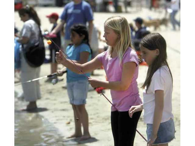 Canyon Country residents Nicole McGrath, 10 (with pole) and friend Ashley Azevedo, 9, fish together at Castaic Lake Saturday morning, during the first annual Castaic Days event.