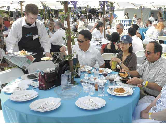 Jonathan Pinkers, left, serves Italian food to Sam and Pauline Yu, and Mehdi Heydari, right, at the Taste of the Town event at Mann Biomedical Park on Sunday to benefit the Child and Family Center.