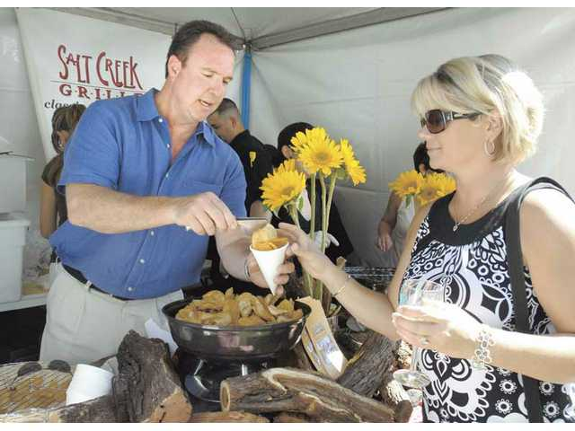 Greg Amsler, left, of Salt Creek Grille, serves signature Salt Creek chips to Juli Marshall at the Taste of the Town event.